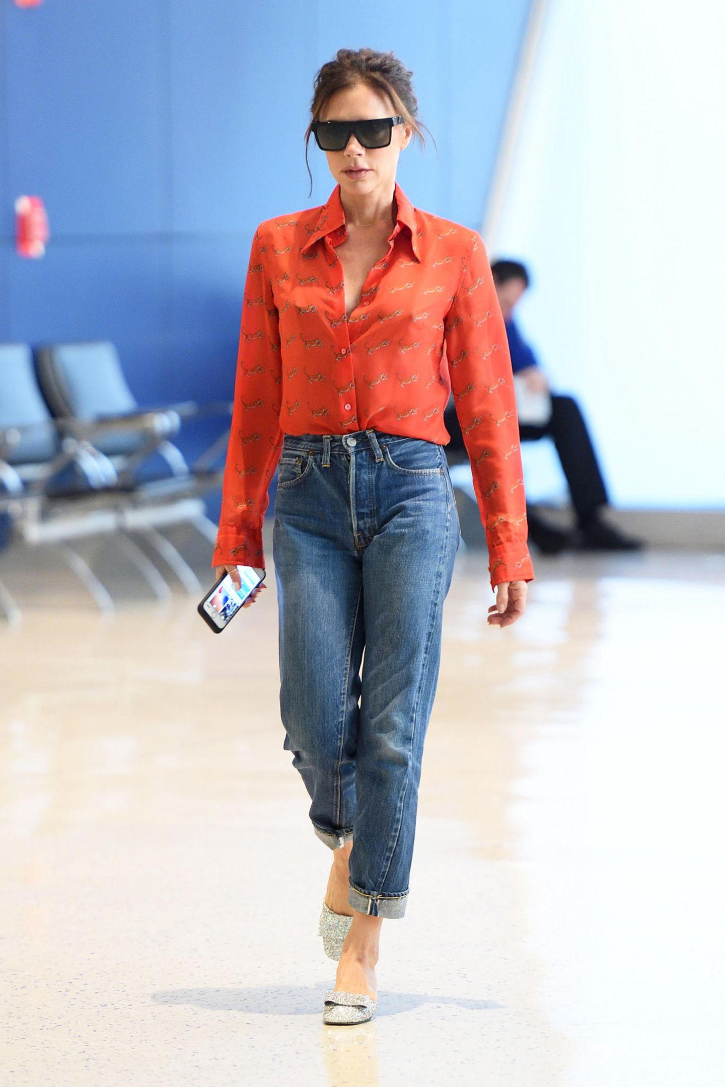 """Ungewohnt lässig flaniert Designerin Victoria Beckham in einer """"Mom-Jeans"""" über den """"JFK Airport"""" in New York. Dazu kombiniert sie eine orangefarbene Bluse, eine """"Posh""""-Sonnenbrille und glitzernde """"Harper""""-Pumps (benannt nach ihrer Tochter) aus ihrer eigenen Kollektion."""