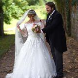 Während die Braut für die offiziellen Hochzeitsfotos noch schnell ihren Schleier zurechtrückt, hält der Bräutigam für seine Liebste den Brautstrauß.