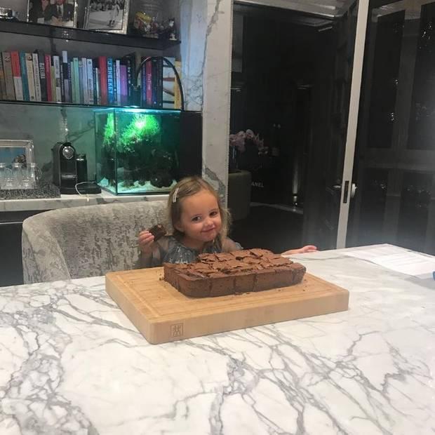 Während Tamara Ecclestone uns eigentlich ihren süßen Backerfolg zeigen möchte, nutzen wir die Gelegenheit um einen Blick auf einen Teil der Küche zu werfen. Eine große Marmortischplatte und gepolsterte Sessel stehen dort; im Hintergrund gibt es ein Regal für Kochbücher und ein Aquarium. Ach ja, guten Appetit kleine Sophia.
