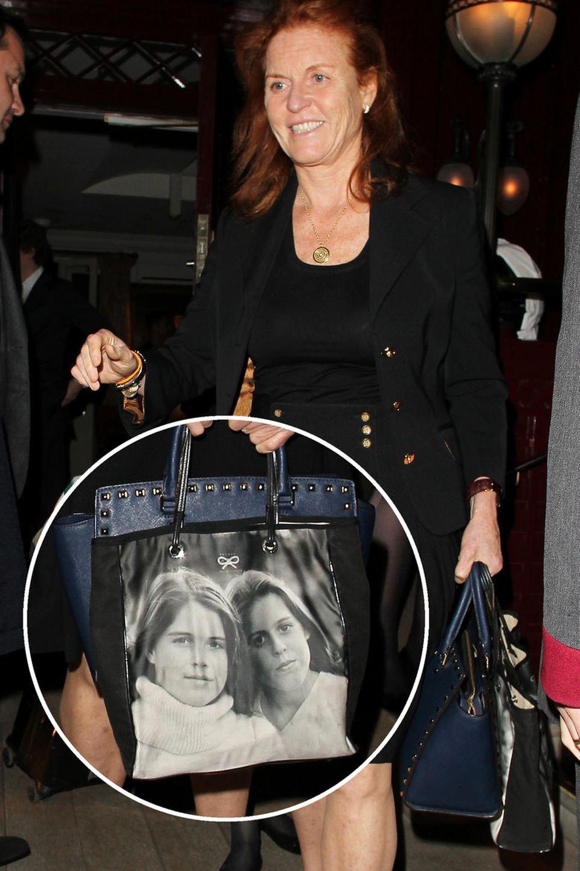 Sarah Ferguson zeigt sich während der Londoner Fashion Week bei einer Party mit einer Tasche, die ein Foto ihrer Töchter Beatrice und Eugenie aufgedruckt hat. Das Modell selbst stammt von der britischen Designerin Anya Hindmarch, bekommt aber durch das Foto einen persönlichen Touch.