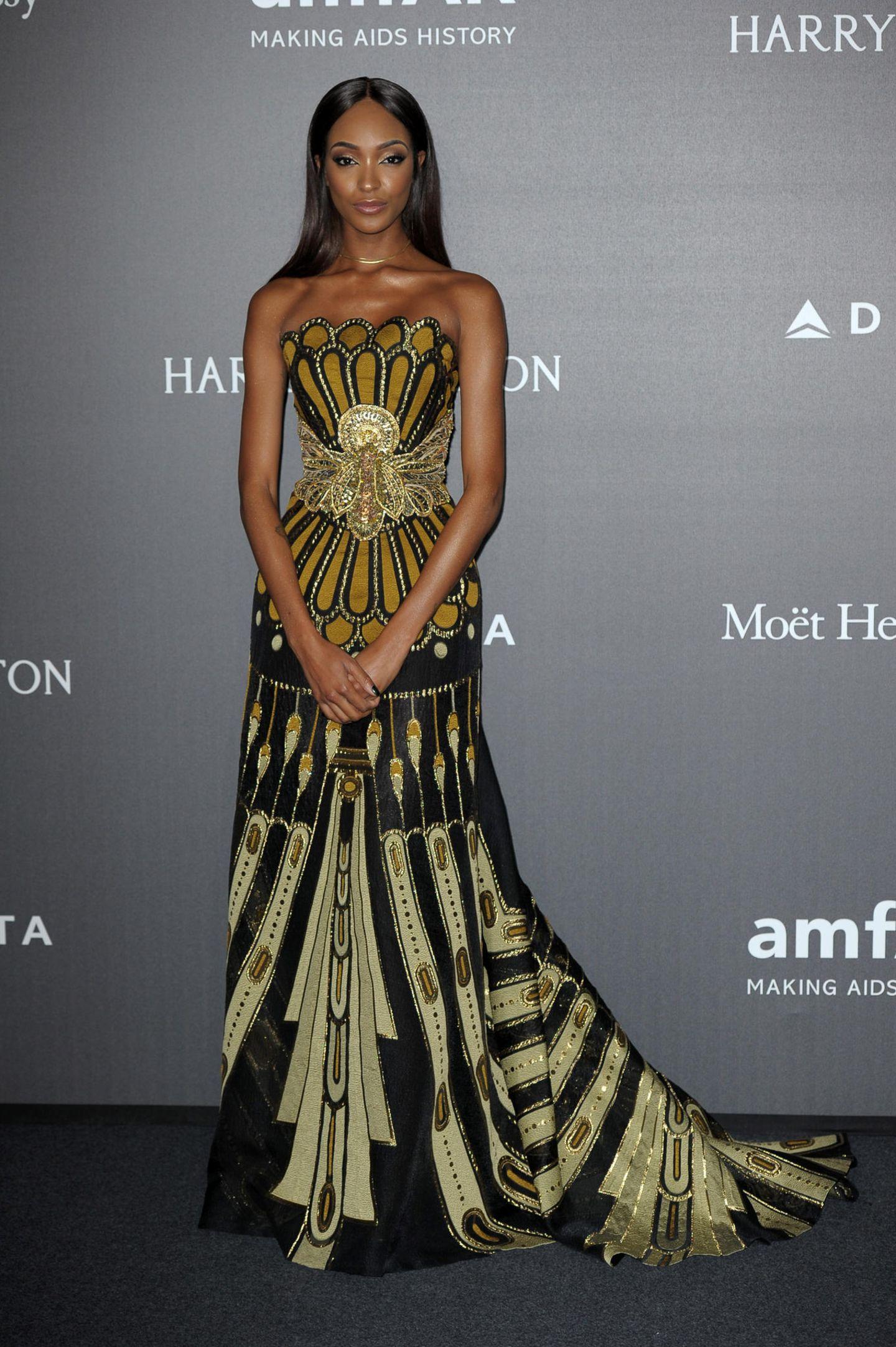Auch Jourdan Dunn trägt schulterfrei. Der figurbetonte Schnitt ihres güldenen Kleides wird durch das grafische Muster noch verstärkt.