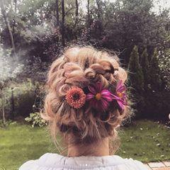 Dreht sich Monica um, entpuppt sich ihre Frisur jedoch als haariges Meisterwerk. In ihre eng anliegenden Zöpfe wurden sogar frische Blumen eingearbeitet.