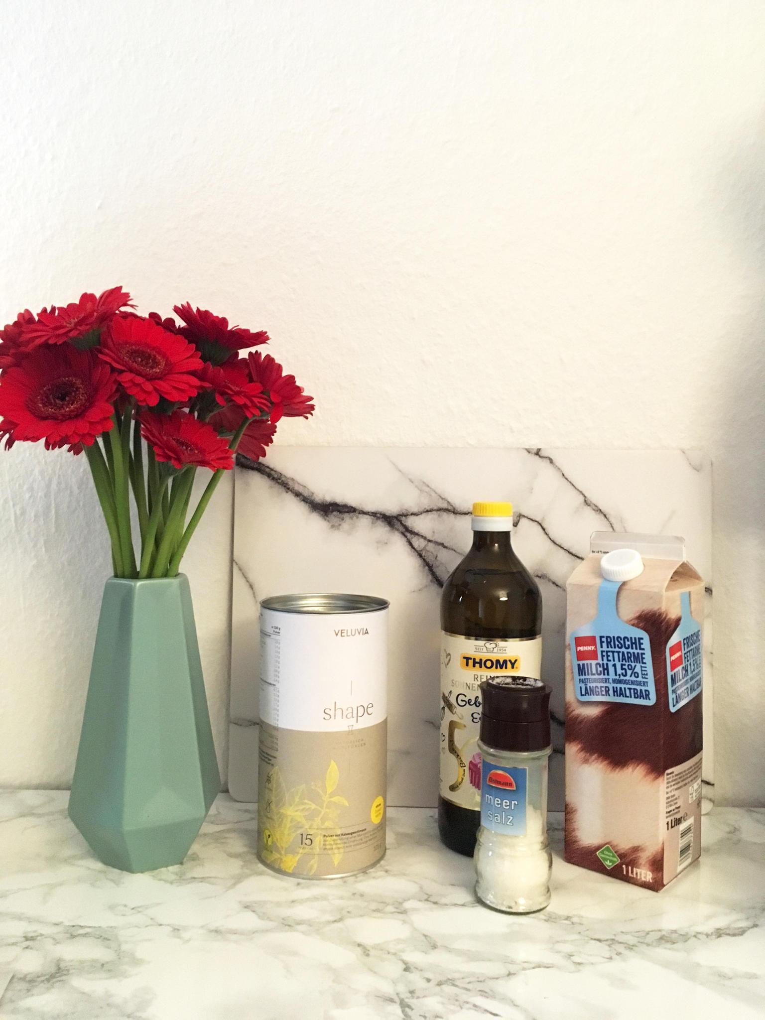 Für den Veluvia-Shake benötigen Sie: Zwei gehäufte Esslöffel des Pulvers, 2g Sonnenblumenöl, eine Prise Salz und 250ml fettarme Milch