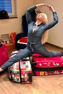 Das soll ihr erst mal einer nachmachen... Im Jeans-Overall sitzt Daniela Katzenberger im Spagat auf ihren Koffern.