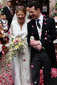 Vor der Kathedrale erwartet das frisch vermählte Ehepaar ein Regen aus Rosenblättern. Jetzt können sie so richtig strahlen und ihr Glück erstmals fassen.