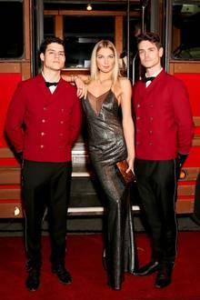 Jessica Hart posiert zwischen zwei Modelkollegen in einem Metallic-Kleid. Dazu kombiniert sie mehrere Armreifen, Ringe und eine Kette von Cartier.
