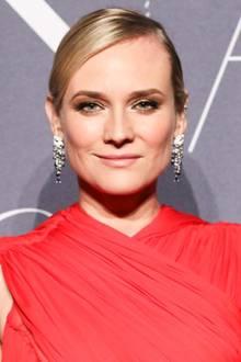 """Diane Kruger erscheint in einem knallroten Kleid, das hochgeschlossen ihren Hals umwickelt. Sie trägt """"Panthère de Cartier""""-Ohrringe mit kleinen Pantherköpfen. Zu ihrem an sich schlichten Outfit das perfekte Accessoire."""