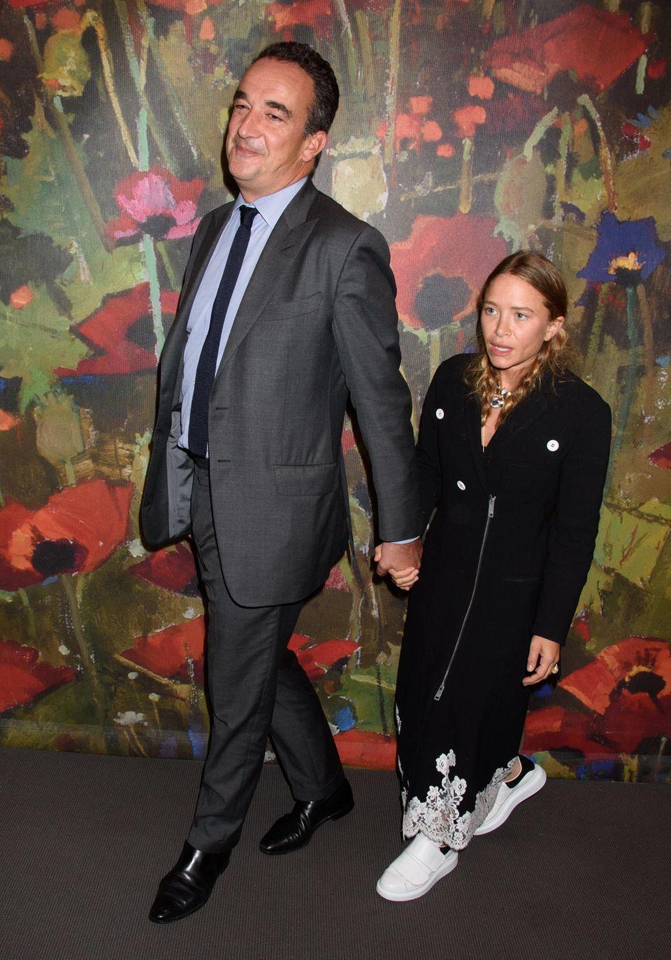 """Außer ihrer Körpergröße, Olivier Sarkozy ist stolze 1,90 Meter groß, während Mary-Kate Olsen bloß 1,57 Meter misst, unterscheidet sie ein Altersunterschied von satten 17 Jahren; und da Mary-Kate Olsen mit ihrer Zwillingsschwester über ein geschätztes Vermögen von 284 Millionen Euro verfügt, darf angenommen werden, dass Mary-Kate ihren französischen Riesen im Designeranzug auch nicht aus, sagen wir mal, praktischen Gründen geheiratet hat. Bleibt nur noch auf einen alten Spruch zurückzugreifen: """"Wo die Liebe hinfällt."""""""