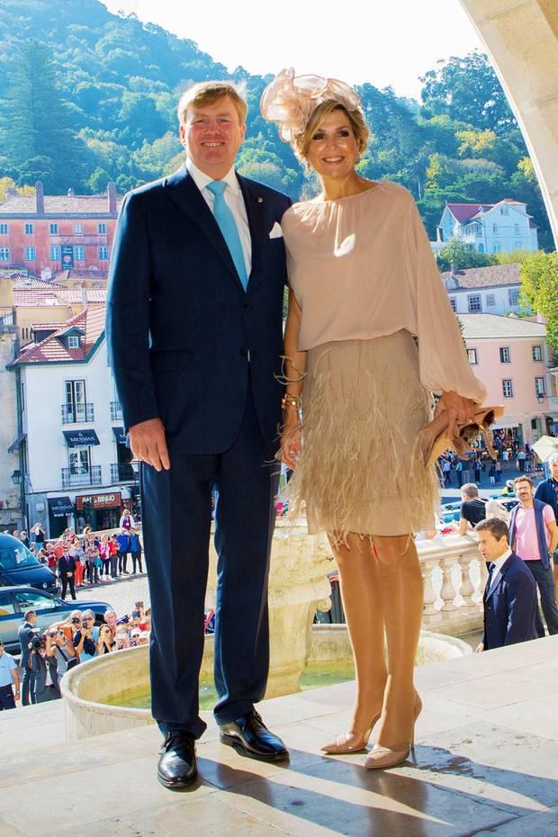 An Tag 3 ihrer Portugal-Reise verzaubert Königin Maxima in einer nudefarbenen Kombination aus Seidenbluse und Federrock. Die farblich abgestimmten Pumps verlängern ihre tollen Beine optisch noch einmal und ziehen nicht nur die Aufmerksamkeit ihres Mannes auf sich