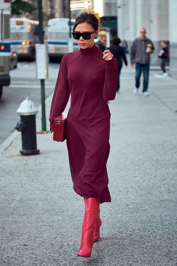 Perfekt für diesen Herbst! Victoria Beckhams bordeauxrotes Kleid aus der eigenen Kollektion kombiniert sie effektvoll mit pinkfarbenen Lederboots.