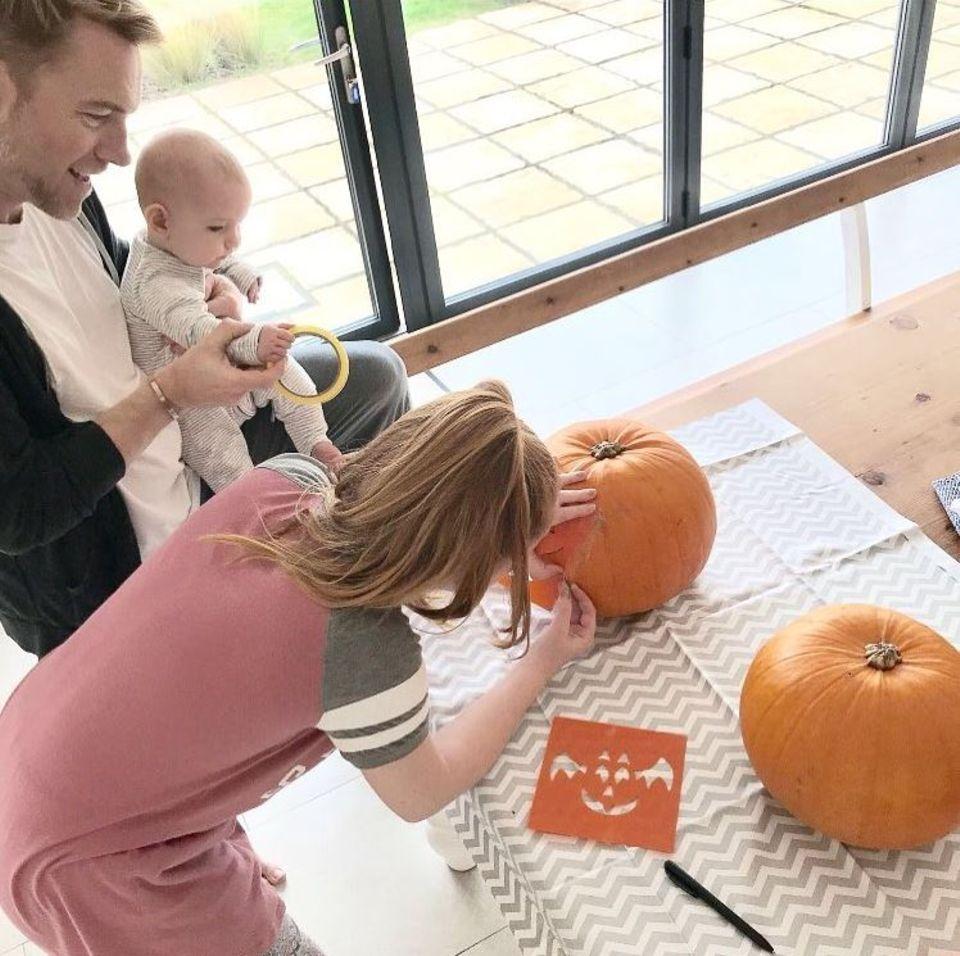 Ali Keating, Tochter des Sängers Ronan Keating (li.), ist in fröhlicher Halloweenlaune: Baby Cooper schaut seiner Halbschwester bei der Kürbisschnitzerei gespannt zu.