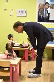 17. Oktober 2017  Der französische Präsident Emmanuel Macron spricht mit Kindern einer Kita nahe Paris. Seine gebeugte Haltung, die Einwegschuhe aus Plastik, der skeptischen Blick des Mädchens und die aufmerksamen Beobachter hinter der Fensterscheibe sorgen für ein herrlich widersprüchliches und gerade deshalb so liebenswürdiges Bild.