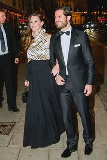 """Bei einem Charity-Dinner in Stockholm glänzt Prinzessin Sofia an der Seite ihres Ehemanns Prinz Carl Philip: Im wahrsten Sinne des Wortes, sie trägt ein gepunktetes Satin-Top und einen schwarzen Maxi-Rock des Stockholmer Labels """"Greta""""."""