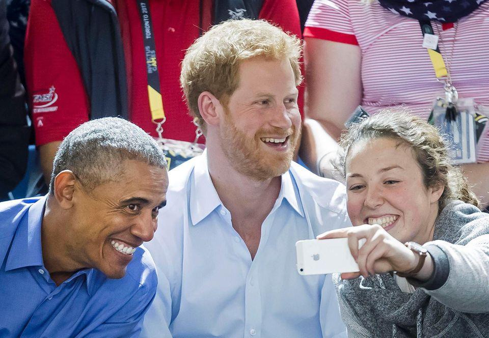 Um dieses Selfie dürften sie viele beneiden: Auf der Tribüne der Invictus-Games erwischt ein Fan Prinz Harry und Ex-Us-Präsident Barack Obama.