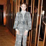 Topmodel Gigi Hadid trägt einen grau-weißen Wollmantel mit auffälliger Chanel-Schnalle. Dazu trägt sie silberne Metallic-Boots und einen Rollkragen-Pullover.