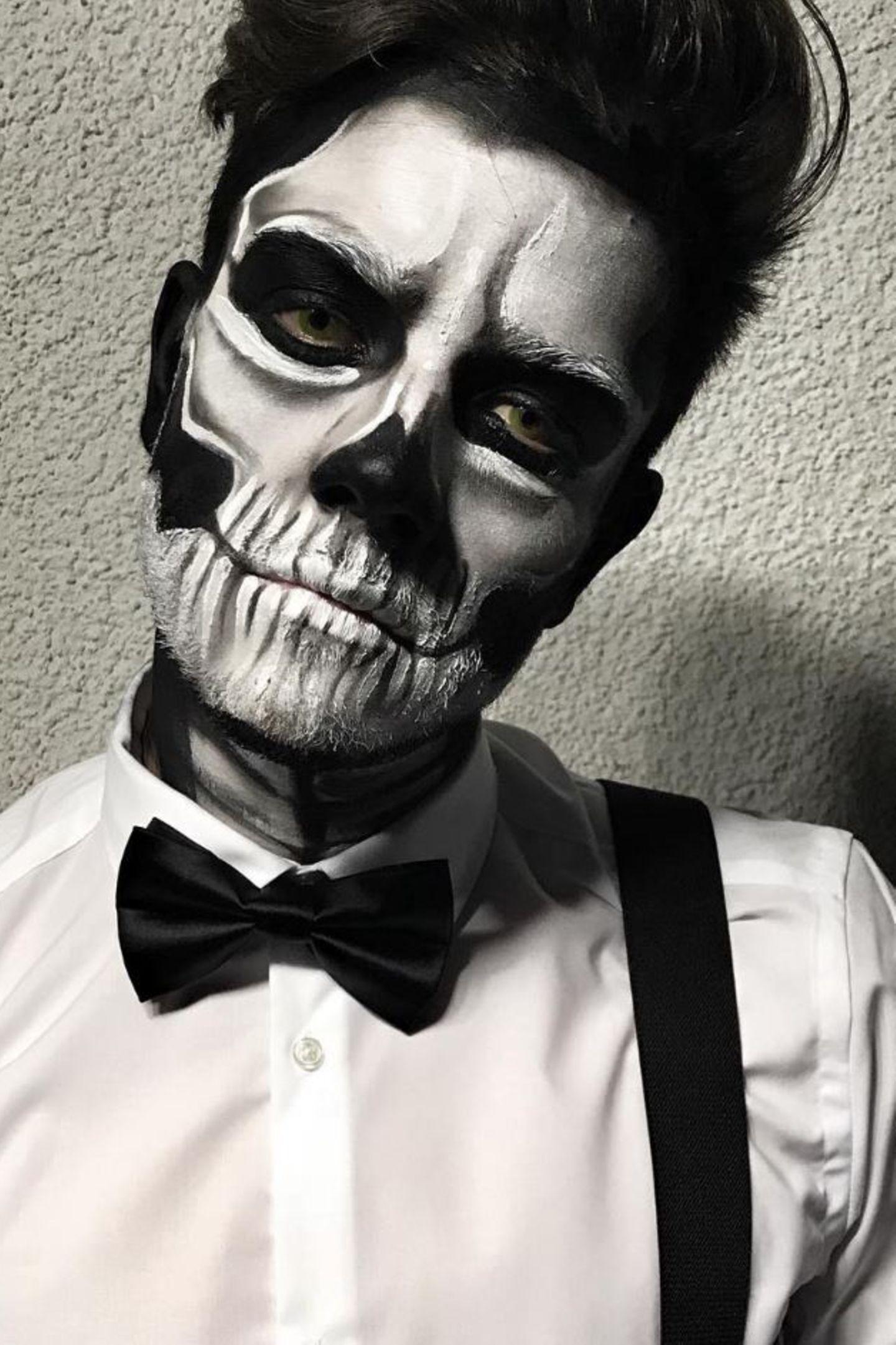 """Erkennen Sie, wer sich hinter diesem Totenkopf verbirgt? Tipp: Die gesuchte Person kommt aus der Schweiz, ist Sänger und Gewinner der Tanzshow """"Dance Dance Dance"""". Es ist Luca Hänni, der sich für eine Halloween-Party in Zürich in die Schwarz-Weiße-Schminke geworfen hat."""