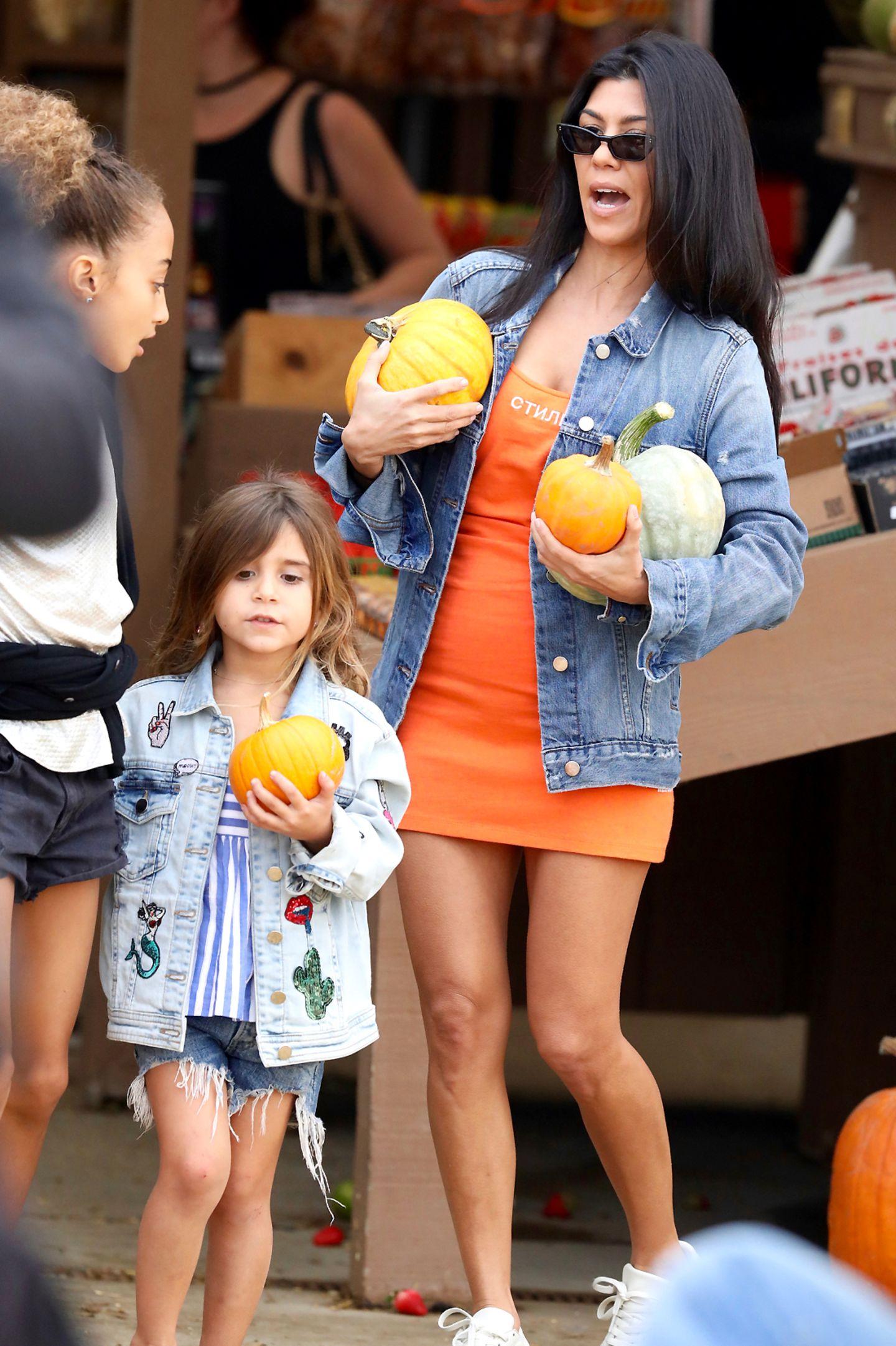 Kourtney Kardashian balanciert mehrere Kürbisse in ihren Armen. Tochter Penelope hat es da mit nur einem Exemplar deutlich leichter.