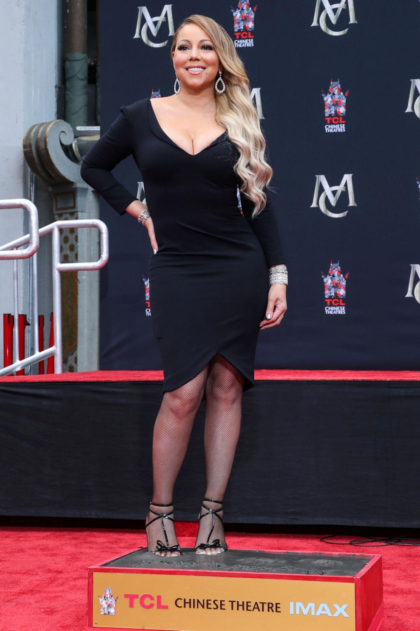 """Mariah Carey zeigt sich in einem knallengen, schwarzen Kleid mit tiefem Ausschnitt und Glitzerklunkern an Ohr und Handgelenken in Los Angeles. Außerdem trägt sie eine Netzstrumpfhose und Riemchen-Heels. Stolz posiert sie für die Fotografen; vor dem """"TLC Chinese Theatre"""" wird sie mit Hand- und Fußabdrücken geehrt."""
