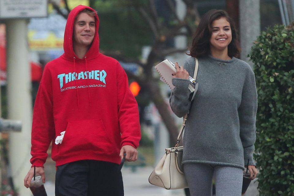 """Das sieht doch ganz nach """"Happy end"""" aus: Justin Bieber und Selena Gomez strahlen bei einem gemeinsamen Spaziergang in lässigen Looks. Er trägt einen roten Hoodie der Skatermarke """"Thrasher"""", sie einen all-over-Stricklook in grau und eine Tasche von Coach. Gerade erst wurde bekannt, dass Selena und The Weeknd sich getrennt haben, da zeigt sie sich immer häufiger mit ihrem Ex-Freund Justin. Jahrelang kämpften die beiden für ihre große Liebe, bis sie sich 2015 trennten - diese Bilder sprechen jedoch für ein Liebescomeback!"""
