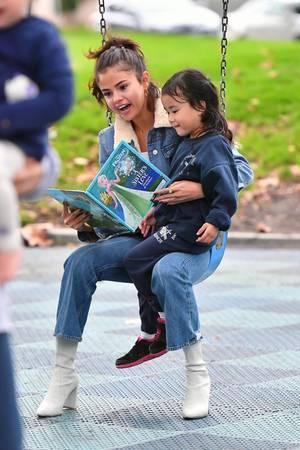 """2. November 2017  Die Schauspielerin und Sängerin wird natürlich schnell erkannt, wie zum Beispiel von diesem niedlichen Mädchen, welches es sich auf Selenas Schoß bequem macht und sich etwas aus """"Die Eiskönigin"""" vorlesen lässt."""