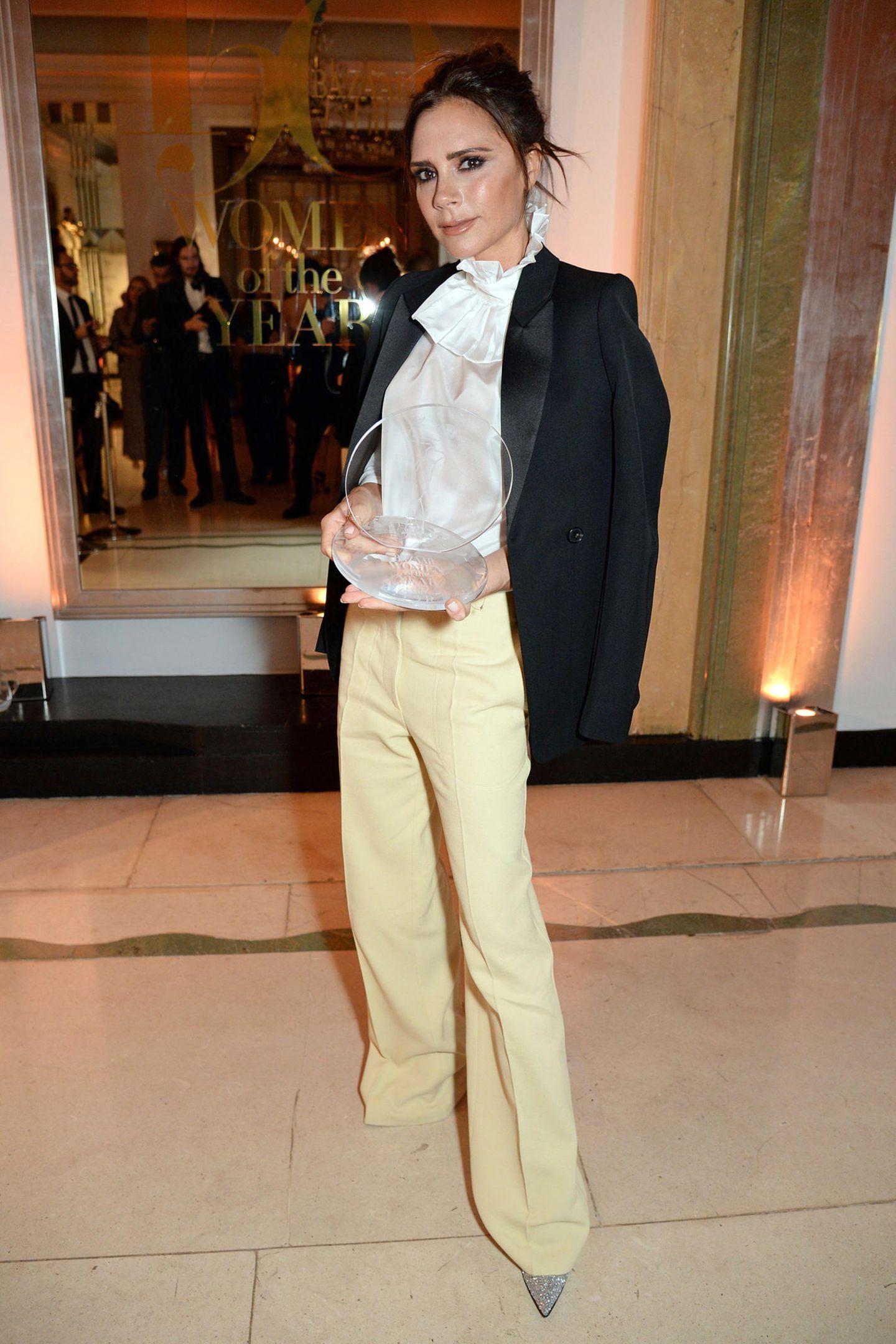 """Bei den """"Woman of the year""""-Awards wurde Victoria Beckham mit dem """"British Brand of the Year""""-Award ausgezeichnet. Sie trägt eine zartgelbe Marlene-Hose, eine weiße, glänzende Bluse und einen schwarzen Blazer. Ein Look, in dem die zierliche Designerin fast unterzugehen scheint."""