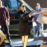 """Im kuscheligen, schwarzen Strickkleid mit Rollkragen kann sich Angelina Jolie gut """"verstecken"""", ihre sehr schlanken Beine setzt sie jedoch in sexy Leder-Boots mehr als deutlich in Szene."""