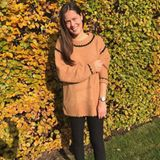 So muss ein Herbst-Look aussehen: In einem oversized Pullover und mit braunen Boots lächelt Ana der strahlenden Herbstsonne entgegen.