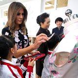 9. November 2017  Melania Trump unterstützt ein Mädchen beim Beschmücken eines Kleids.