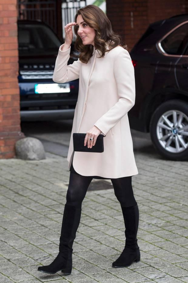 In einem kurzen Mantel und mit schwarzen Stiefeln besucht die schwangere Herzogin Catherine ein Londoner Kinderzentrum. Der A-liniege Schnitt des Mantels kaschiert ihr wachsendes Babybäuchlein geschickt und die Stiefel lenken die Aufmerksamkeit auf ihre schlanken Beine. Ein toller Look!