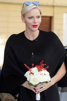 Im schlichten, schwarzen Cape und mit auffälligem. roten Lippenstift wird Fürstin Charlène vor dem Gebäude des Roten Kreuzes in Monaco mit weihnachtlichem Blumenstrauß begrüßt.