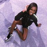 Leomie Anderson macht es sich in ihren Sportsachen auf dem lila Glitzerlaufsteg bequem.