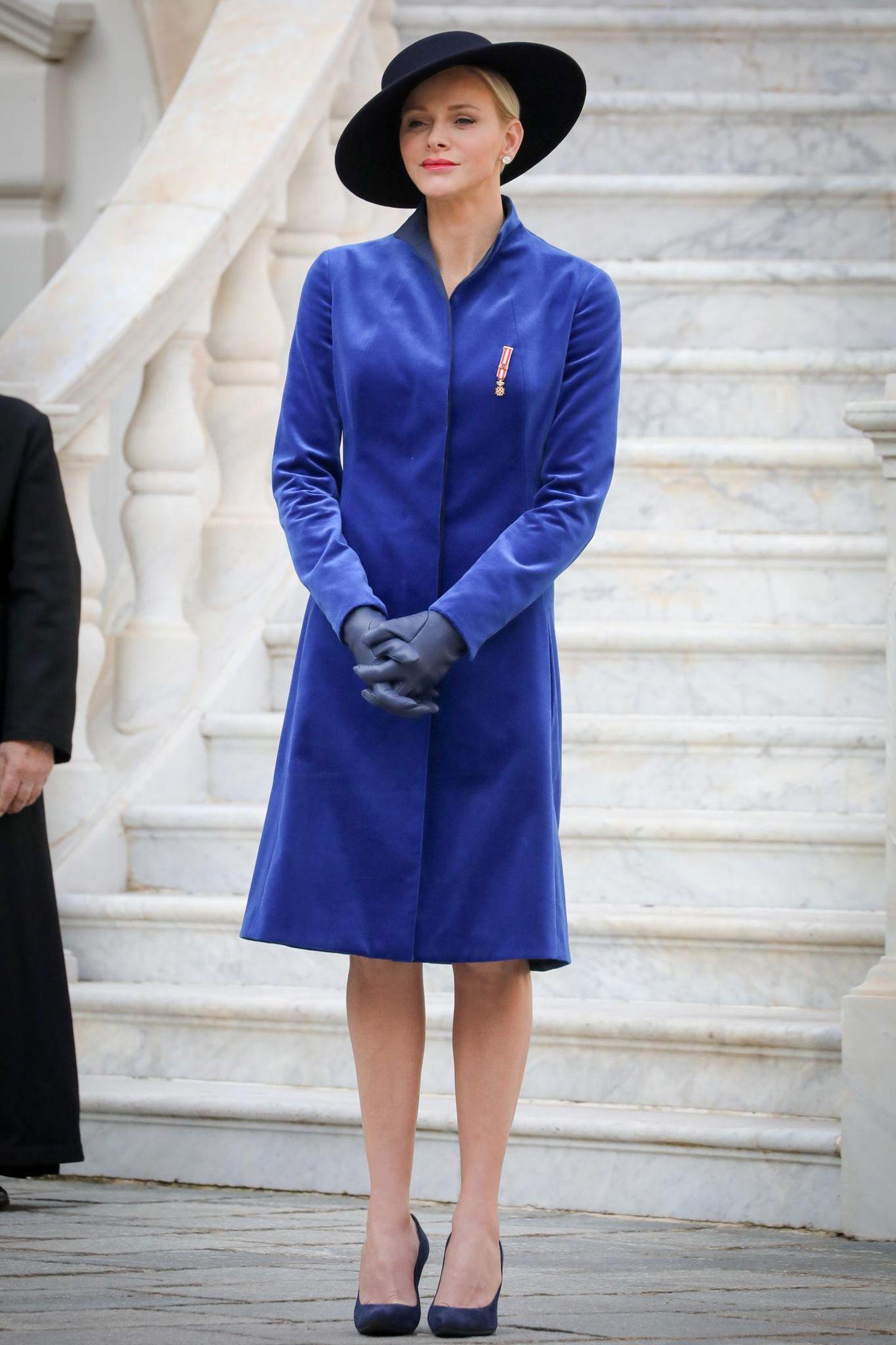 Am Nationalfeiertag Monacos sticht Fürstin Charlène vor den weißen Marmorstufen des Palastes in ihrem blauen Mantel von Akris wundervoll hervor. Der samtige Stoff wirkt dabei besonders royal.