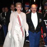 Für die Gala am Abend des Nationalfeiertags wechselt Charlène ihre Garderobe und tauscht den blauen Mantel in ein hellbeiges Ensemble ein. Die Schärpe macht den Look offiziell und sorgt für den Farbtouch.