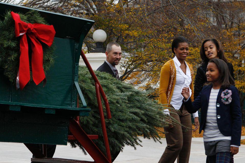 Michelle Obama (Mitte) und ihre Töchter Malia Obama (r.) und Sasha Obama (vorne) begutachten den Weihnachtsbaum, der vor das Weiße Haus geliefert wird