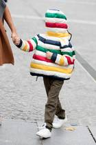 Diesem Knirps ist ganz schön langweilig, daher macht er lieber Faxen und hat sich seine Jacke falsch herum angezogen. Doch um welchen Star-Sprössling handelt es sich?