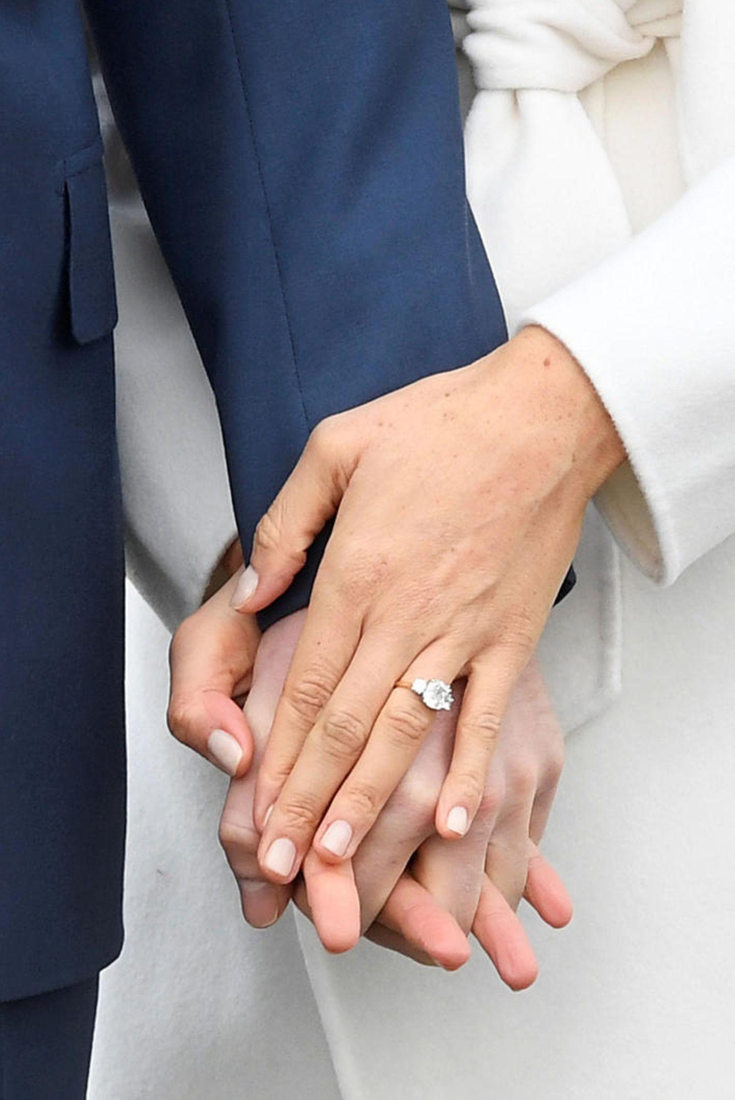 Den Verlobungsring hat Prinz Harry tatsächlich persönlich gestaltet. Der Diamantring funkelt mit einem großen Stein in der Mitte umrandet von zwei kleineren Steinen, die aus einem Schmuckstück von Prinzessin Diana stammen.
