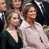 Sara Hellqvist, Taufpatin und Schwester von Sofia trägt dunkelgrüne Seide. Prinzessin Madeleine hingegen hat versteckt ihr florales Valentino-Kleid und auch ihren Babybauch unter einem rosafarbenen Mantel.