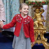 Farblich abgestimmt mit Mama Victoria trägtPrinzessin Estelle eine rote, florale bestickte Wolljacke über dem grauen Kleid,