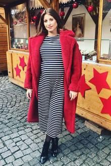 """""""Ringel Ringel Reihe am Christkindelmarkt..."""", schreibt Cathy Hummels zu diesem schönen Schnappschuss auf Instagram. Ihre Babykugel hüllt die Moderatorin in ein gestreiftes Kleid, das sie zu einem roten Teddy-Mantel kombiniert."""