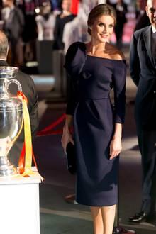 """Was für ein strahlender Auftritt: Anlässlich des 50. Jubiläums und einer Preisverleihung des Sportmagazins """"AS"""" glänzt Königin Letizia in einem dunkelblauen, figurbetonten Kleid mit raffiniertem Schnitt von Delpozo. Dieses Label trägt auch Melania Trump gerne. Besonders schön kommt die große Schleife durch ihre hochgesteckten Haare und ein kräftiges Make-up zur Geltung."""