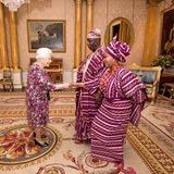 6. Dezember 2017  Queen Elizabeth empfängt George Adesola Oguntade aus Nigeria mit seiner Frau zu einer Privataudienz im Buckingham Palace. Dabei sind alle Augen auf die traditionelle Kleidung der Gäste gerichtet, die perfekt mit dem Kleid der Queen harmoniert.