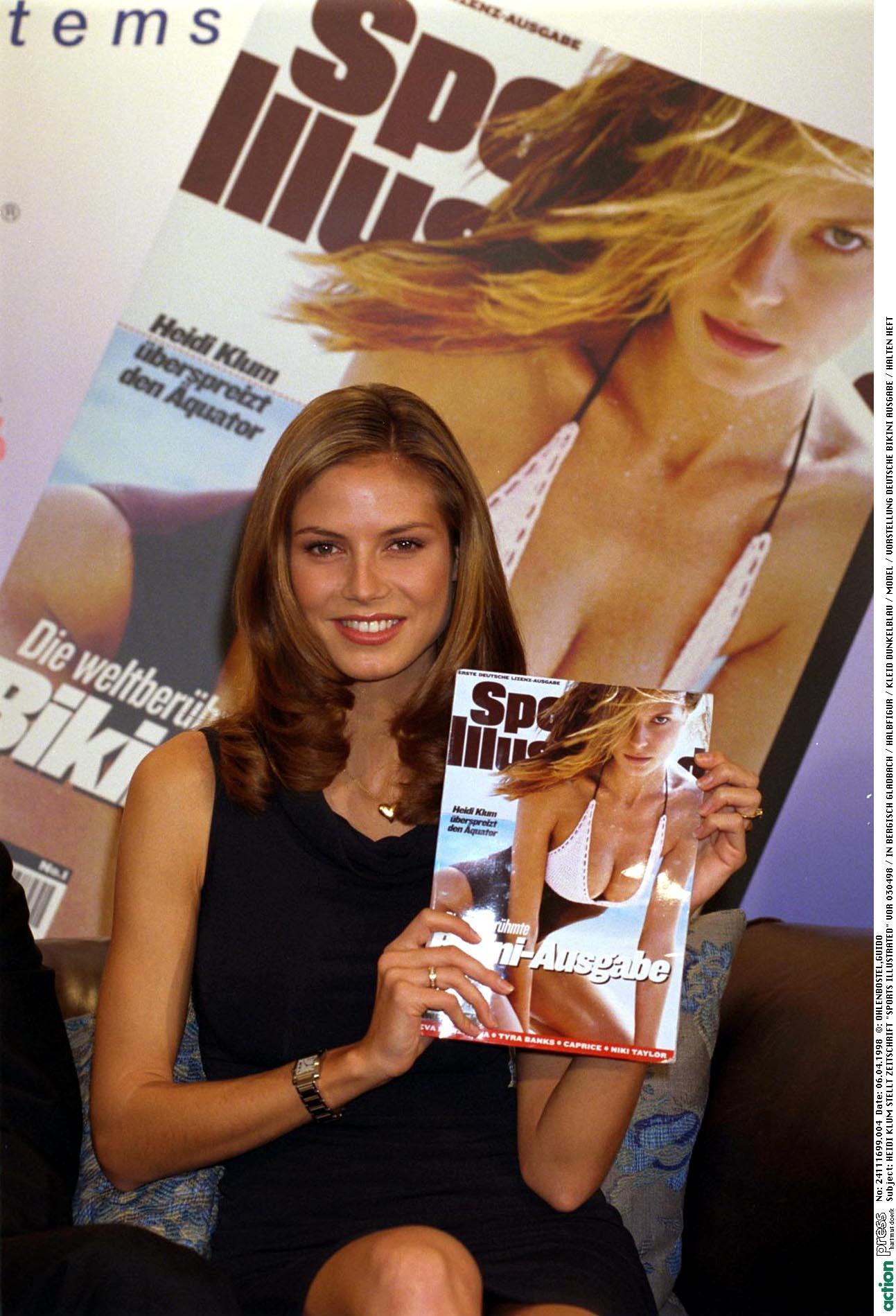 """Heidi Klum posiert mit der """"Sports Illustrated"""", auf deren Cover sie 1998 zum ersten Mal zu sehen ist."""