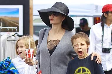 Ja, finden wir auch, Knox, dieser Look ist echt zum Schreien. Mama Angelina Jolie sieht beim Flohmarktbummel mit ihren Kids so aus, als hätte sie sich die knielange, graue Strickjacke nur schnell über das schwarze Spitzen-Nachthemd geworfen, Schlapphut und schwarz-goldenen Slipper machen den Schlabber-Look perfekt.