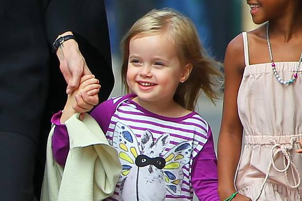 Wie ein blondes Engelchen: Vivienne im zarten Alter von drei Jahren im März 2012. Mit lilafarbenem Longsleeve und Ballerinas in glitzerndem Rot spaziert sie mit Angelina Jolie und Adoptivschwester Zahara durch New Orleans. In ihren Ohrläppchen funkeln Ohrringe.