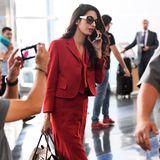 """Amal Clooney ist eine echte Stilikone und ist stets perfekt gestylt. Zu einem roten Kostüm kombinierte die erfolgreiche Anwältin die """"Bancroft"""" Bag von Michael Kors Collection. Eine Handtasche, die aktuell extrem beliebt bei den Stars ist."""