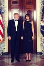 Mit diesem Foto wünschen Donald und Melania Trump ganz offiziell frohe Weihnachten. Melania trägt ein schwarz-glitzerndes Cocktailkleid vom spanischen Label Delpozo. Dazu trägt sie schlichte schwarze Pumps.