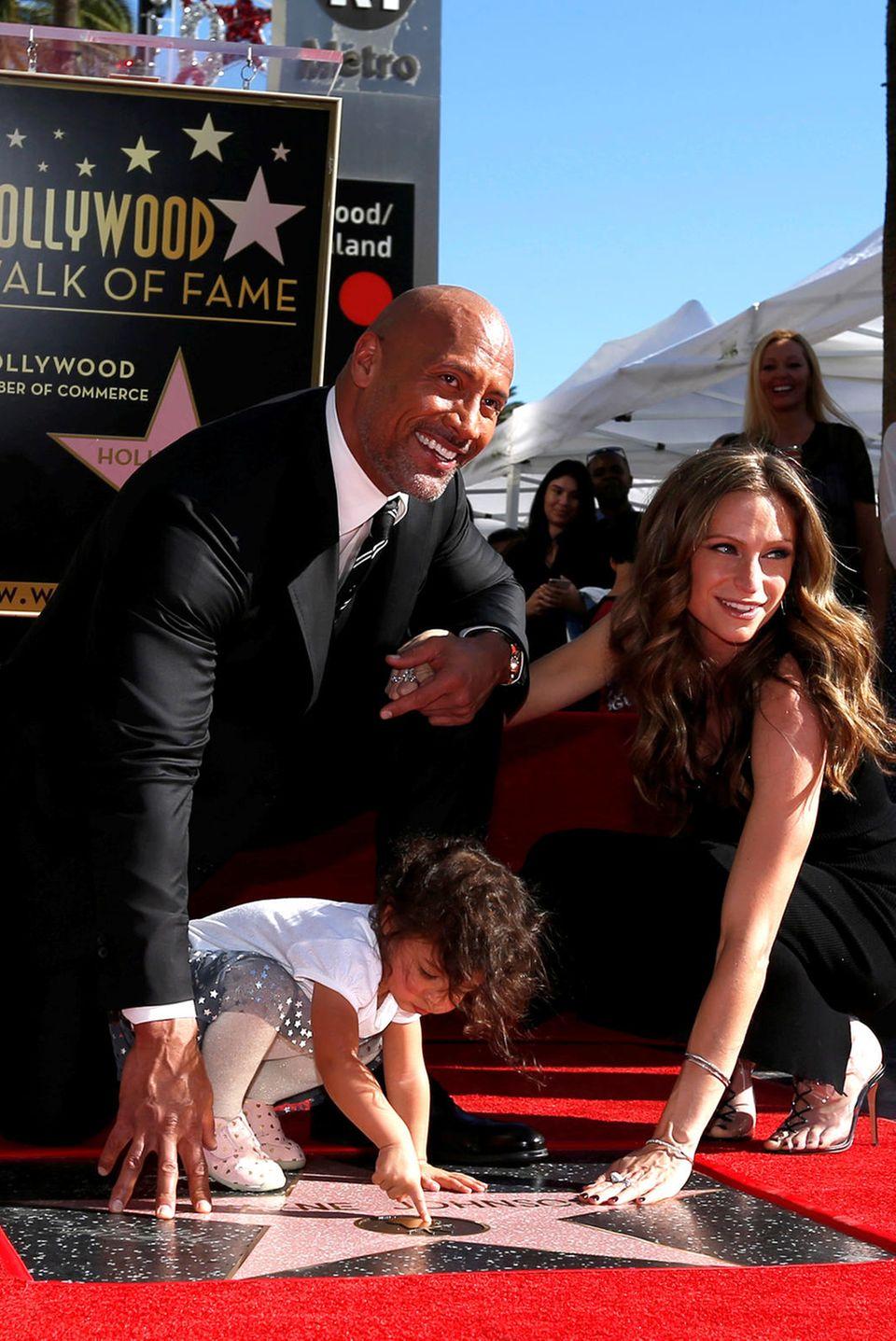"""13. Dezember 2017  Dwayne Johnson wird in Hollywood mit einem Stern auf dem berühmten Walk of Fame geehrt. Unterstützung bekommt """"The Rock"""" an diesem besonderen Tag von seiner Frau Lauren Hashian und Tochter Jasmine Lia."""