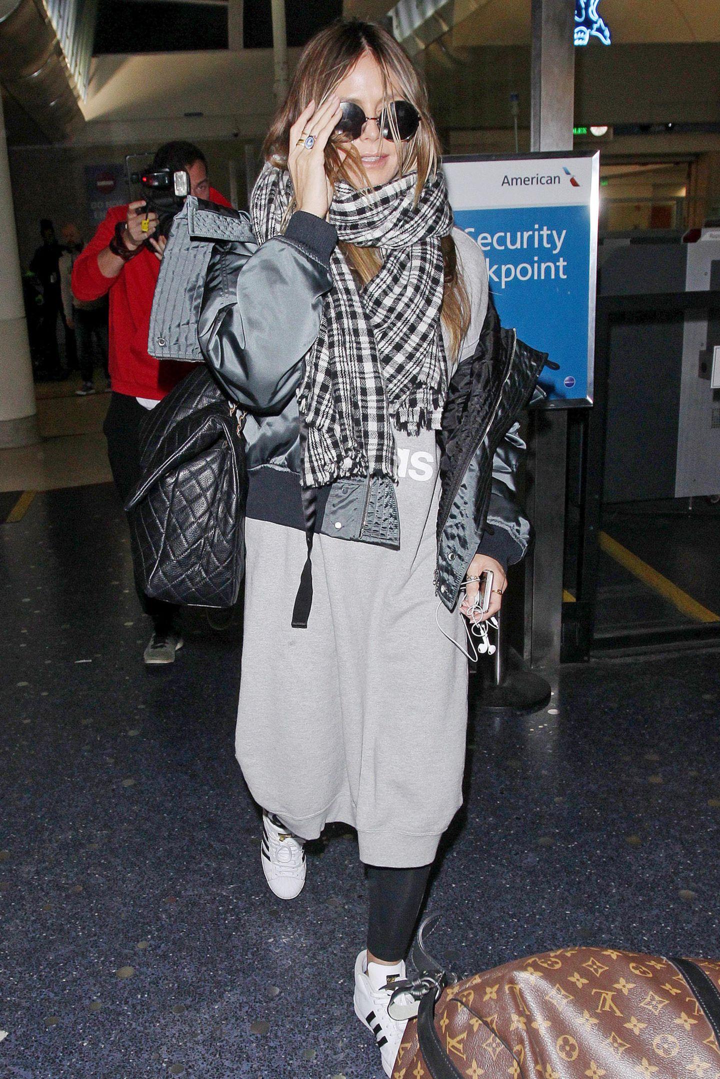 Dick verpackt und doch erkannt: Heidi Klum sieht sich im sportlichen, grauen Winter-Look und extragroßem Karo-Schal am Flughafen von L.A. doch wie üblich von vielen Paparazzi umgeben.