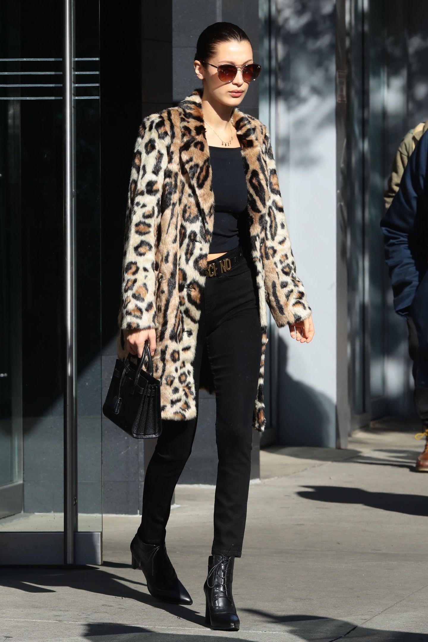 Bella Hadid beweist mit ihrem Look, dass ein Leo-Mantel selbst das düsterste Outfit zum Hingucker machen kann. Ein cooler Gürtel, eine tolle Tasche und schlichte Stiefel runden alles ab.