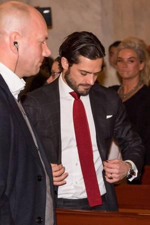 Immer wieder wird Prinz Carl Philip von Schweden dabei fotografiert, wie er an den Knöpfen seines Anzugs zupft.